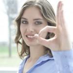 junge frau zeigt mit fingern o.k. und lacht