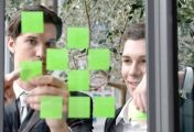 zwei kollegen zeigen bei meeting auf post it auf scheibe